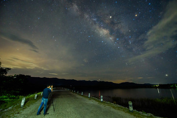A man taking photos the Milky way over reservoir with mountain night