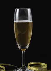 Champagne isolated black background, gold ribbon
