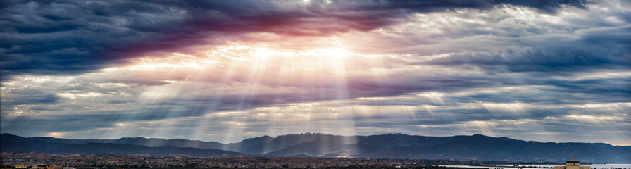Beam of light through the clouds on the mountains - Rays of light shining through dark clouds , dramatic sky with cloud
