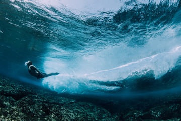 Man swimming underwater over a shallow reef