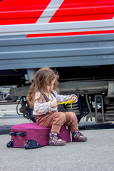 Little girl sitting at suitcase on railway station with the train on background.