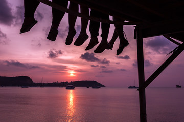 Group of friends sitting on the dock of the bay enjoying lovely sunset in the island of Koh Samui, Thailand