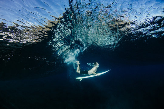 Man swimming with surfboard in sea