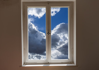 Closed window and a view of a clouds on a sunny day