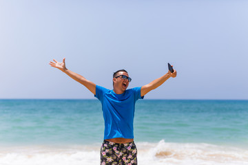 Young man hold cellphone take picture of summer beach panoramic sea view
