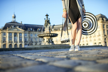 Tourist holding a photocamera standing on the famous Bourse square with beautiful buildings and fountain in Bordeaux city during the morning