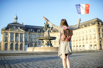 Young woman tourist enjoying morning view on the famous Bourse square standing back with french flag in Bordeaux city in France