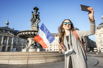 Young woman tourist making selfie photo with french flag on the famous de la Bourse square in Bordeaux city