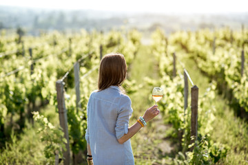 Wall Murals Vineyard Young woman with wine glass standing on the beautiful vineyard during the sunset