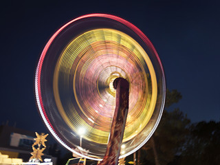 Illuminated rotating carousel in the evening park