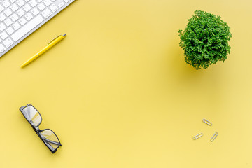 Manager workplace in office with keyboard, glasses and plant on yellow table background top view copyspace