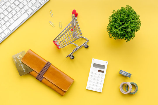 Online shopping. Bank card in purse nearby keyboard and mini shopping cart on yellow background top view