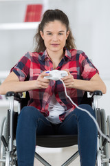 girl on wheelchair playing video games at home