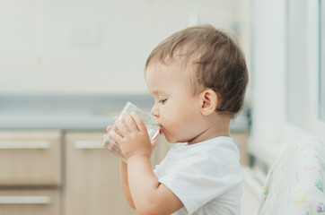 A boy drinks water in the kitchen