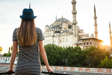 A young tourist girl with a beautiful figure looks from the hotel terrace to the world famous blue mosque Sultanahmet in Istanbul, Turkey. Travel, sightseeing, rest, relaxation.