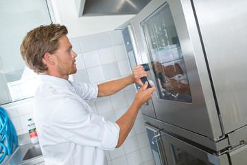 Chef at door of industrial oven