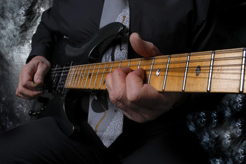 neck of guitar with arm and hand playing the strings