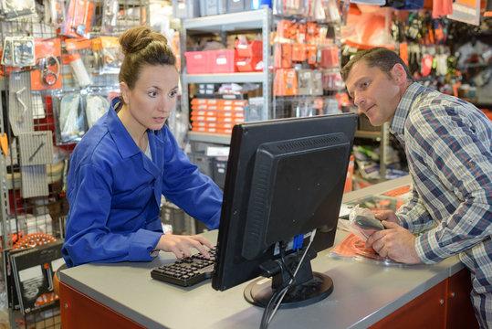 Customer glancing at shop keeper's computer