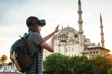 A traveler with virtual reality glasses. The concept of virtual travel around the world. In the background, the blue mosque Sultanahmet in Istanbul in Turkey. Future technology concept.