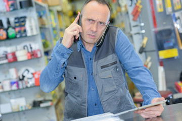 Retailer on telephone, puzzled expression