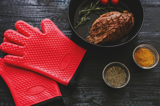 Stylish rubber gloves and fried steak in a hot frying pan.