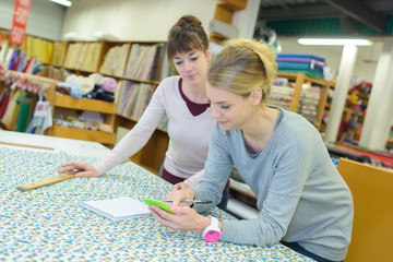 Women in textiles shop calculating amount