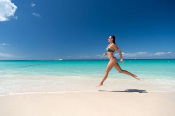 Woman in sexy swimsuit running on sea beach
