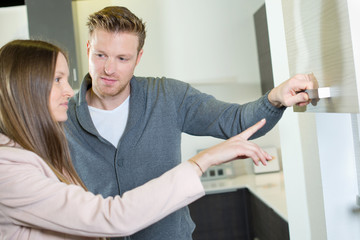 Couple looking at kitchen cupboards