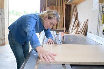 Woman aligning wood to circular saw