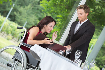 Waiter making recommendation to woman in wheelchair