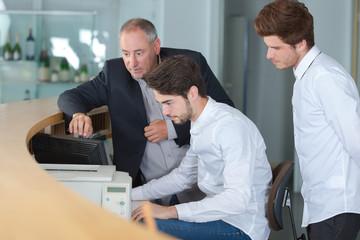Three men looking at computer behind reception desk