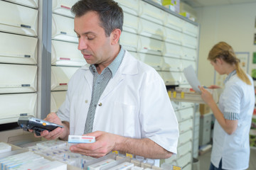 Pharmacist checking medication on electronic device