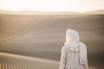 Jesus Christ looks out toward the sand dunes as the sun sets in the background. Wall mural