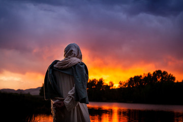 Jesus Christ stands beside a lake and watches the sun sets over the water. Wall mural