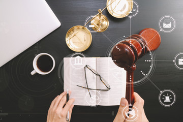 justice and law concept.Top view of Male judge hand in a courtroom with the gavel and brass scale and computer and open bible book on dark wood table with Vr diagram