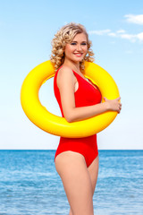 Beautiful blonde in a red swimsuit holds a life buoy. It is on the beach.