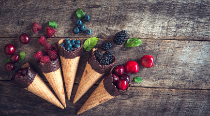 Fresh berries in the ice cream cones on wooden background with blank space