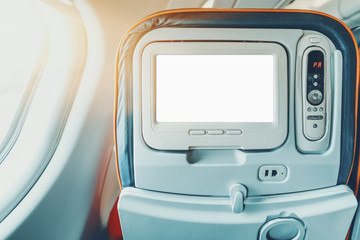 Empty white mock-up of aircraft multimedia screen with remote control, close-up view of blank placeholder of airplane monitor filled with solid white in passenger seat, multiple buttons and sockets