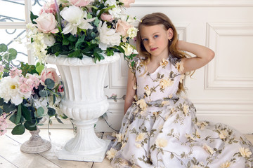 girl in floral dress sitting on the floor next to a white stone vase flowers wall