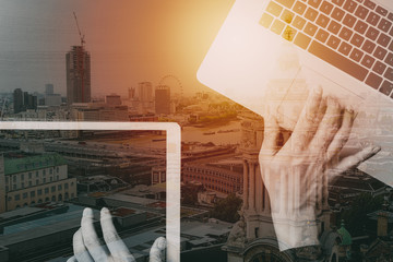 cyber security internet and networking concept.Businessman hand working with  laptop computer and digital tablet background with buildings exposure