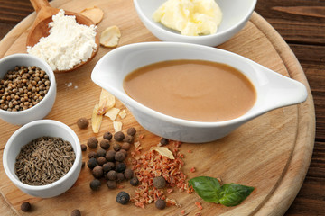 Tasty turkey gravy in sauce boat and spices on wooden board