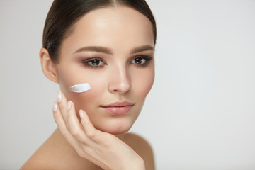 Beautiful Woman Face With Cream On Fresh Soft Skin. Cosmetics