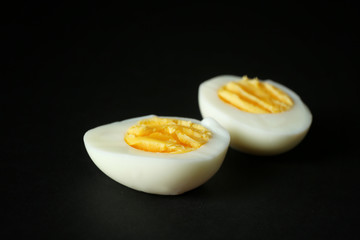 Sliced hard boiled egg on black background. Nutrition concept