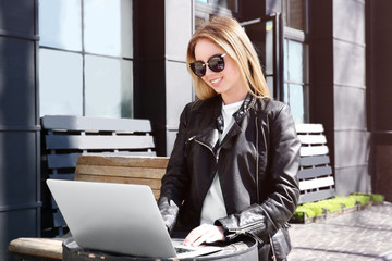 Young blond girl in sunglasses using laptop outdoors