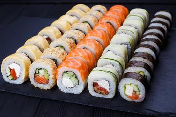 In de dag Sushi bar Colorful delicious set of sushi served on black slate, close up. Japanese cuisine, restaurant menu photo.