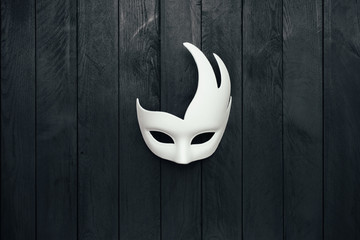 White mask on black wooden wall. Swan. Copy space.