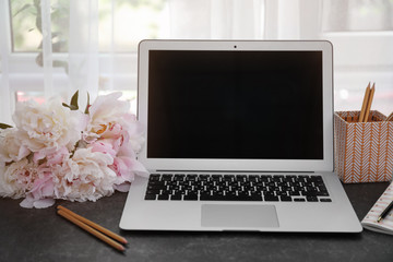 Bouquet of beautiful peony flowers, laptop and stationery on table