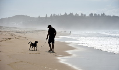 Dog and his owner walking on Belmont beach (Central Coast, NSW, Australia)