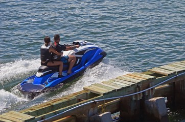Young boy and girl riding tandem on a jet ski in the florida intra-coastal waterway.