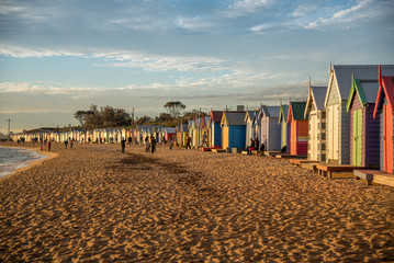 Tourists walk pass colorful bathing boxes at Brighton Beach near Melbourne, Australia.